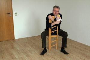 Porträt mit Stuhl und Buch.